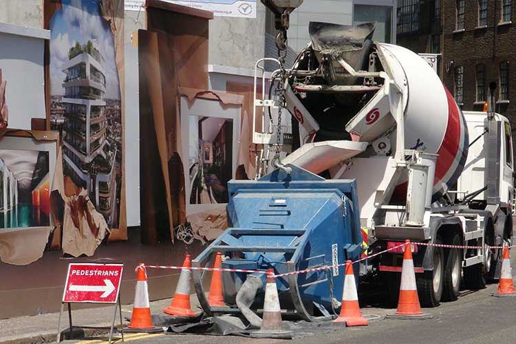 concrete skip being filled with concrete from a concrete truck